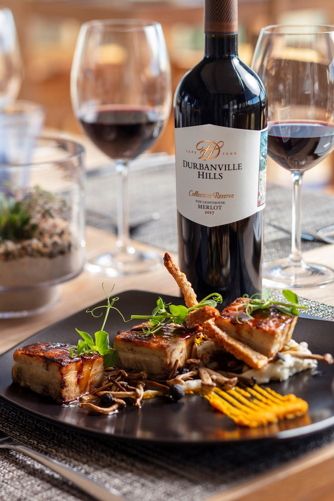 Durbanville Hills Collectors Reserve Lighthouse Merlot 2017 paired with pork belly on a black plate